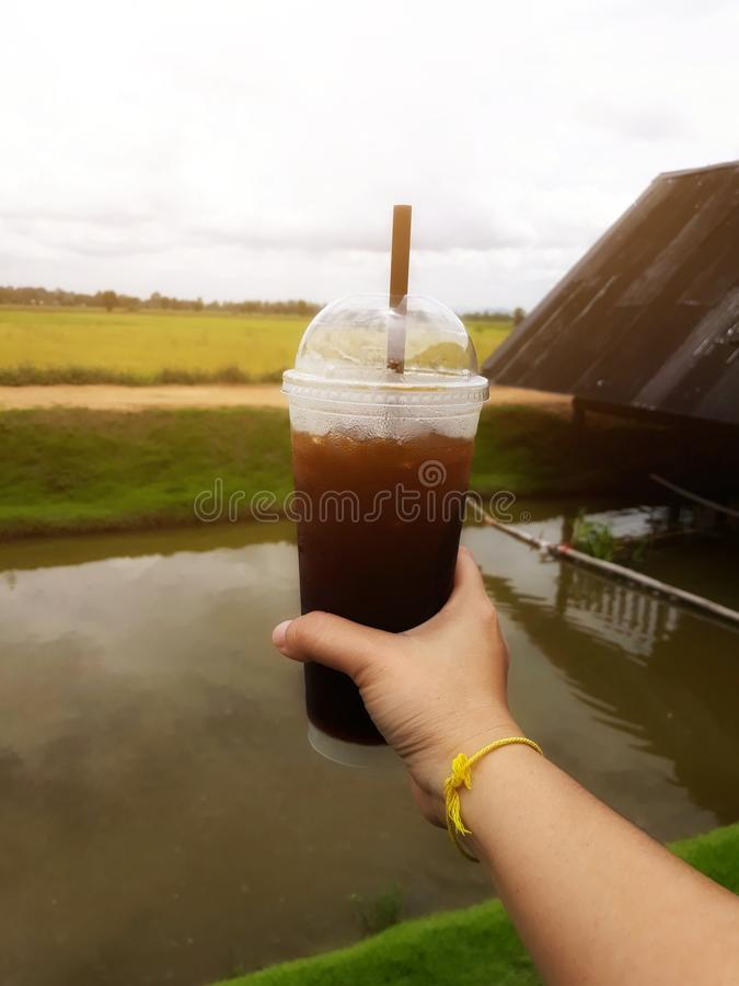 Close-up pictures of people holding a coffee cup  America cool glass plastic background rice fields sky  Holiday drink concept stock images