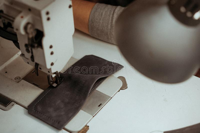 Close-up of a piece of leather lying on a sewing machine on the table in the workshop. Handmade master at work in local. Workshop. Handmade concept. Leather stock images