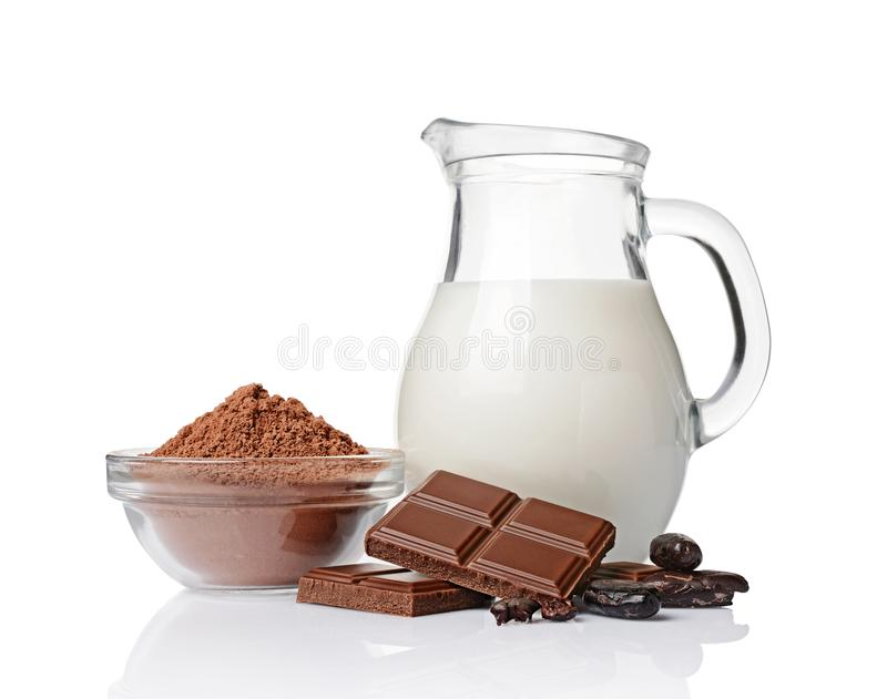 Close-up pieces of chocolate bar with cocoa beans, bowl of cocoa powder and glass jug of milk royalty free stock image