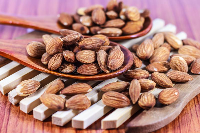 Close up pile of Almonds pour from wood spoon on wood background, Almonds perfect for a diet for a healthy diet stock photo