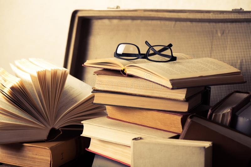 Close up of a pile of books and a pair of. Books erudition literature information knowledge education wisdom royalty free stock photo