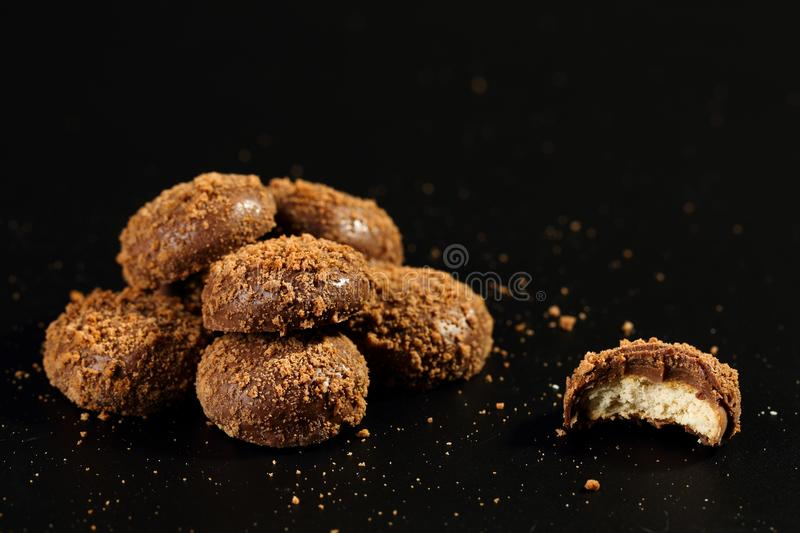 Close up of a pile and half bitten delicious crunchy caramel biscuits coated with milk chocolate and biscuit particles royalty free stock image