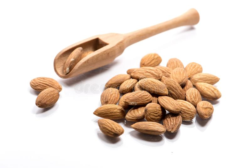 Close-up of pile of raw almond nuts in a wooden spoon on white b stock photo