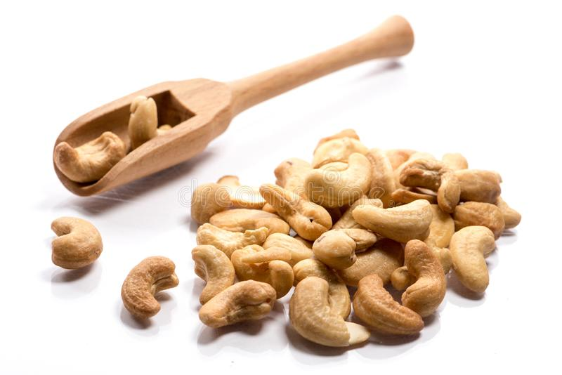 Close-up of pile of roasted, salted cashew nuts in a wooden spoon on white background stock images