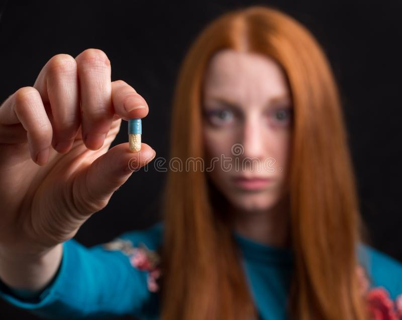 Afraid woman looking at pill. Close up of pill in hand of afraid young woman on black background stock photo