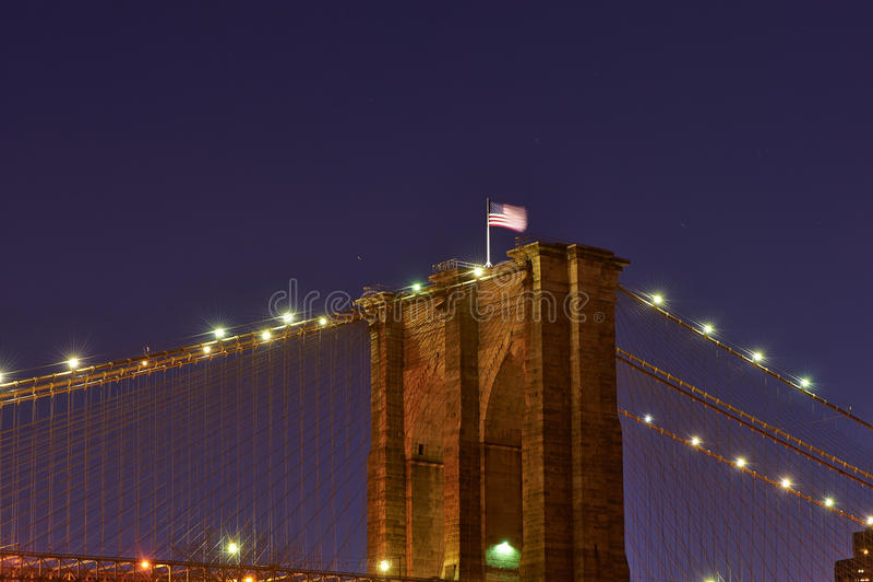 Close up of a pillar of the Brooklyn bridge with flag at night stock photos