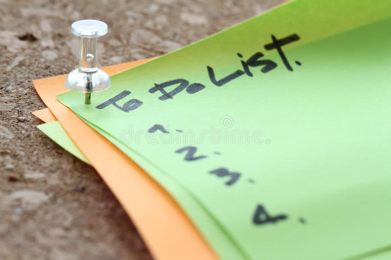 close up on pin and to do list word on sticky note with cork boa stock photo