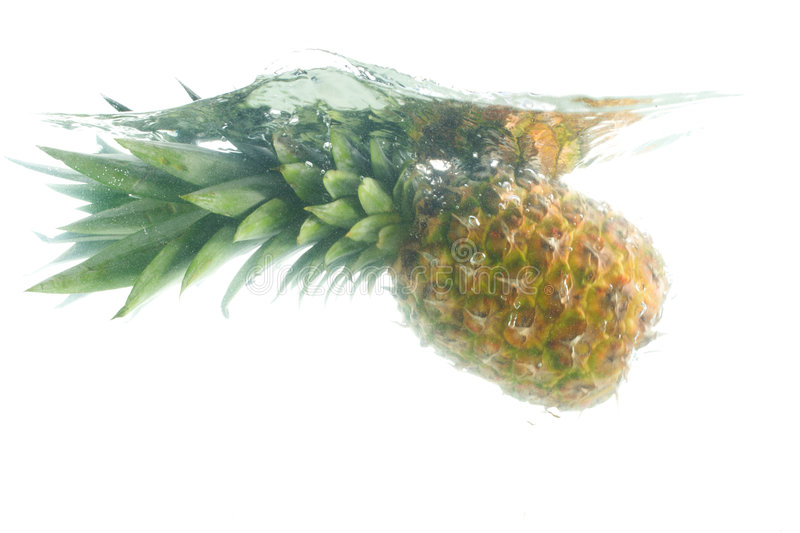 Close-up pineapple falling in water. Isolated on white stock photography