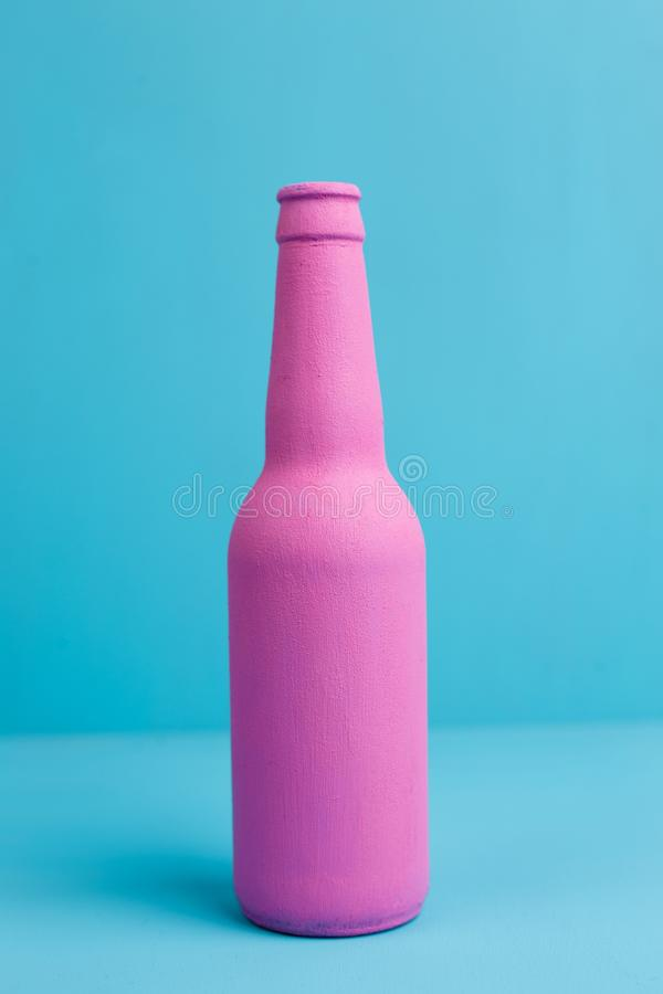 Close up of pink beer bottle on blue background. Deceptive attra. Ction of alcohol. Alcoholism addiction, alcohol abuse and alcohol dependence concept stock images