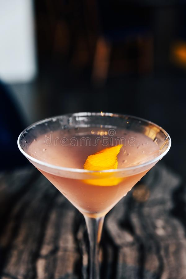 Close-up Pink cocktail filled a sliced of Yuzu peel in wine glass on marble top table royalty free stock photos