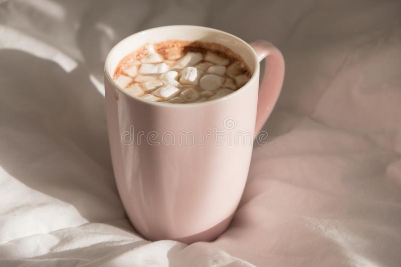 Close up pink cup of hot chocolate with marshmallows on the bed. Good morning, world.  royalty free stock photo