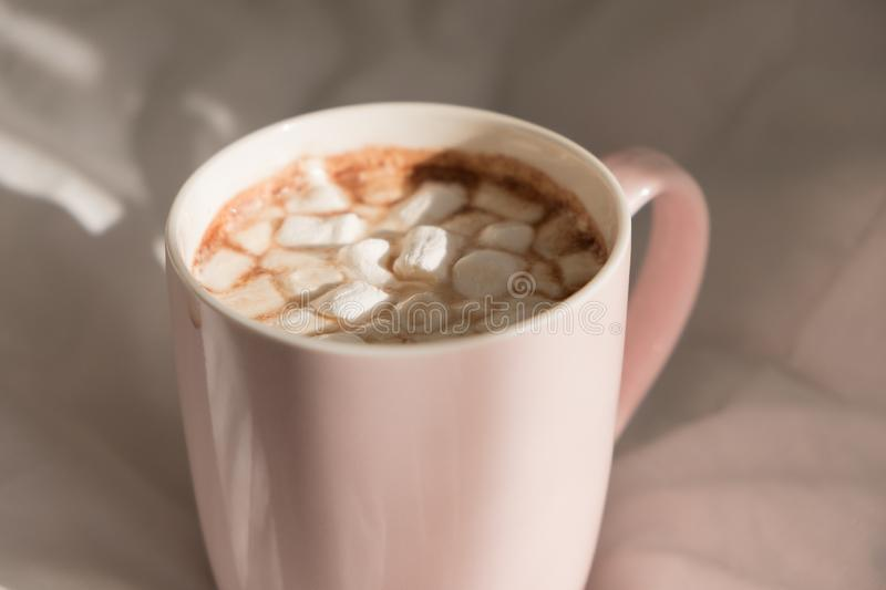 Close up pink cup of hot chocolate with marshmallows on the bed. Good morning, world.  royalty free stock photos