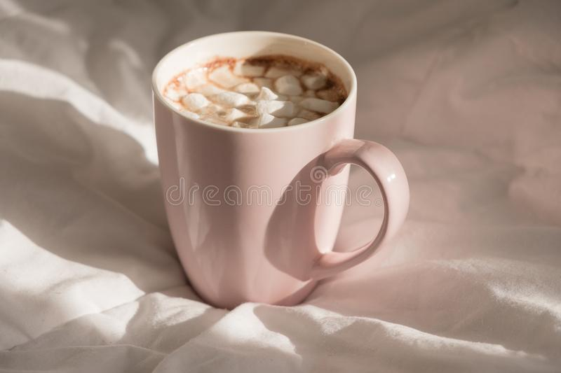 Close up pink cup of hot chocolate with marshmallows on the bed. Good morning, world.  royalty free stock image