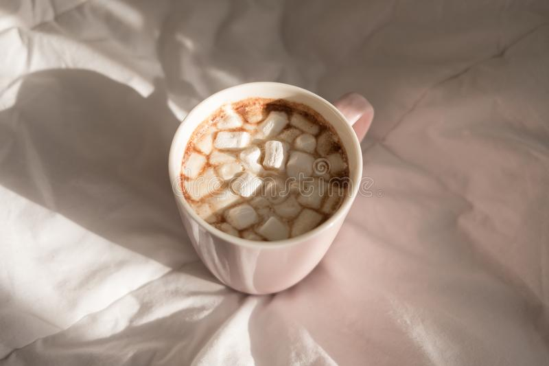 Close up pink cup of hot chocolate with marshmallows on the bed. Good morning, world. Top view royalty free stock images