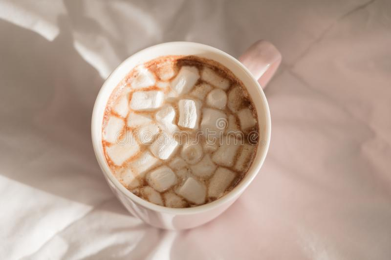 Close up pink cup of hot chocolate with marshmallows on the bed. Good morning, world. Top view stock photography