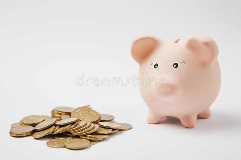Close up of pink piggy money bank, pile of golden coins on white wall background. Money accumulation stock image