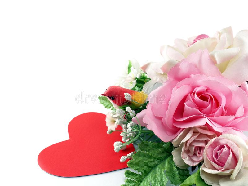 Close-up pink rose flowers with green leaves and colorful little bird and red heart card isolated on white background. Artificial flower wreath gift for royalty free stock photos