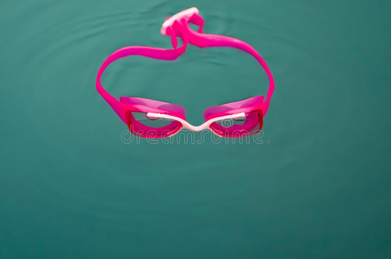 Close-up of  pink  swim goggles in  water. Close-up of  pink  swim goggles in  water  of  interior swimming pool royalty free stock photos