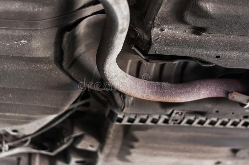 Close up pipe exhaust rusty iron under car with lift background royalty free stock photo