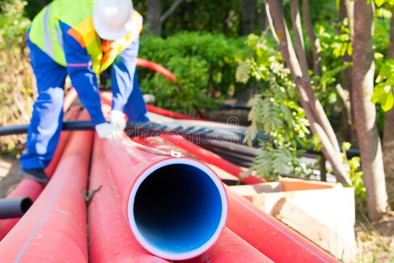 Close-up of a pipe hole, meter for measurement is fixed on top, against the background of a worker royalty free stock photos