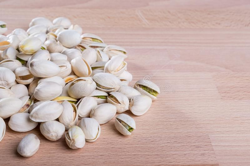 Close up Pistachio nuts with shell on wooden floor background royalty free stock photography