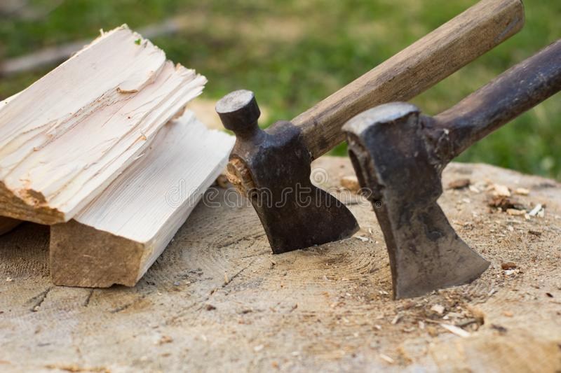 Close up piture of chopping firewood, country photo with wood and axe. Sawmill on mountains forest, tools for chopping wood and many dry logs royalty free stock photo