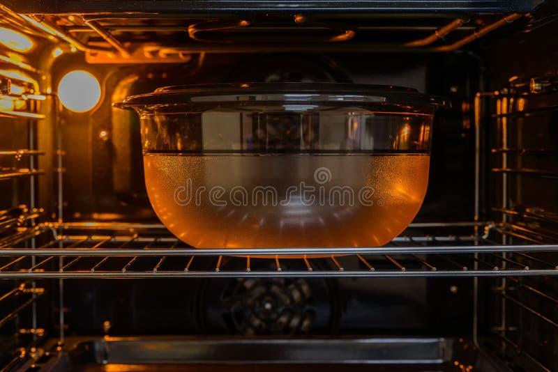 Close up plastic bowl inside oven. Closeup image of plastic bowl inside working modern oven stock image
