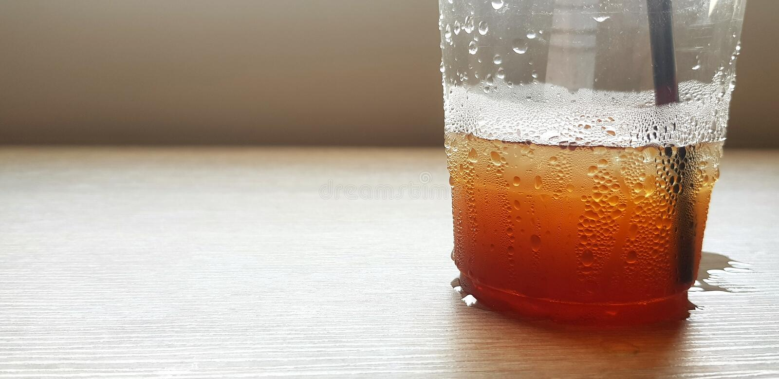 Close up plastic glass of water, iced coffee, coke or cola and straw putting on wooden table  with copy space. Refreshment, Cold, Thirsty, Drinking, Object stock photography