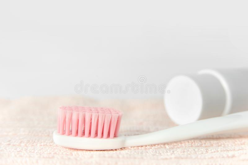 Close up of plastic white toothbrush with pink bristle and toothpaste in tube on pink towel. royalty free stock images