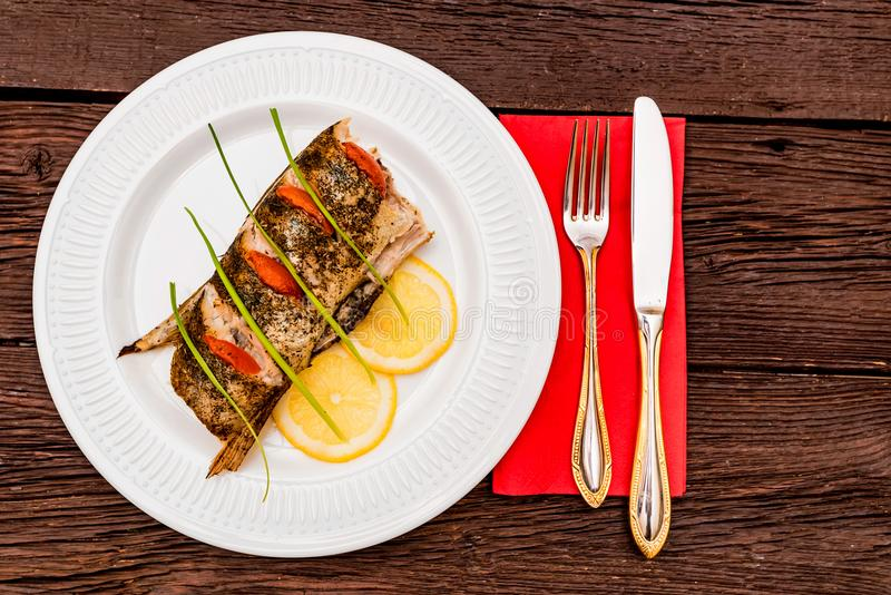 Roasted zander fillet with asparagus and lemon. Close up plate with pike perch fillet, lemon, tomato and asparagus. Healthy diet concept stock images