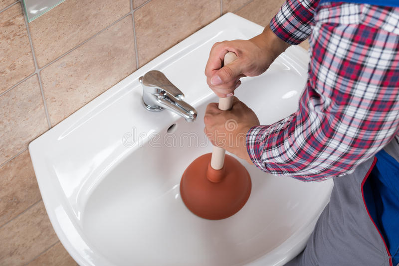 Plumber Using Plunger In Bathroom Sink. Close-up Of A Plumber Using Plunger In Bathroom Sink royalty free stock photos