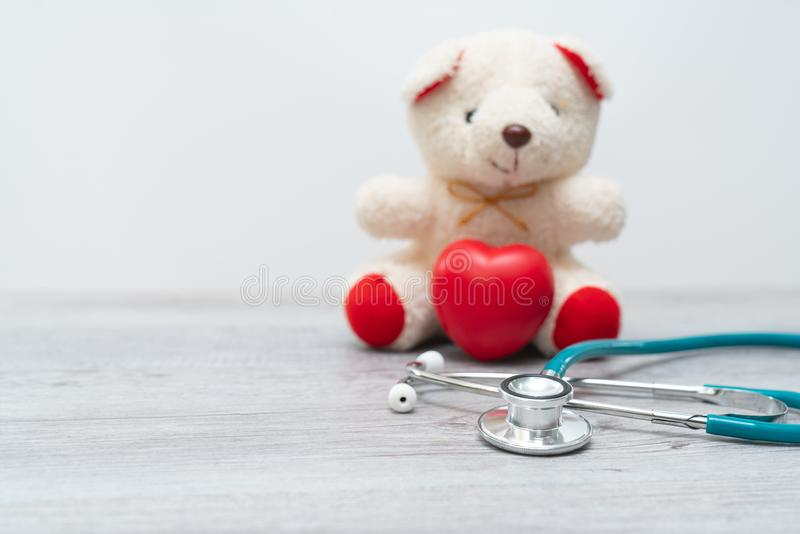 Close up Plush Teddy Bear with Stethoscope Device on Top of a Glass Table, Emphasizing Copy Space. royalty free stock photo