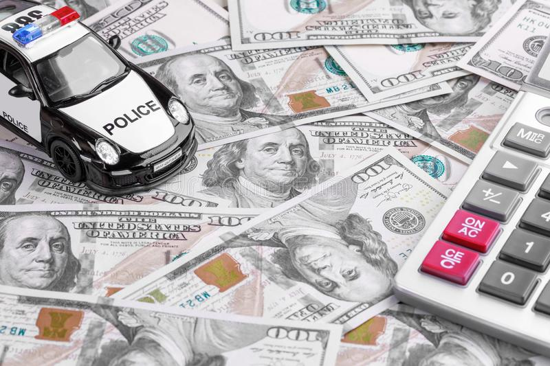 Close-up of a Police Car Model with Calculator on Dollar Notes royalty free stock images