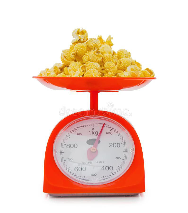 popcorn on red weigh scales isolated on white background royalty free stock photo