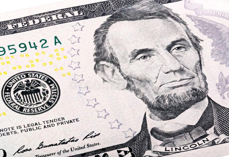 Close-up portrait of Abraham Lincoln end print of Federal Reserve System on five-dollar bill. stock photo