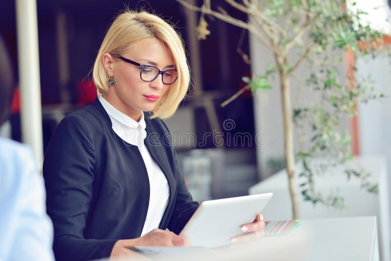 Close-up portrait of active business woman holding laptop while standing at office. royalty free stock photos