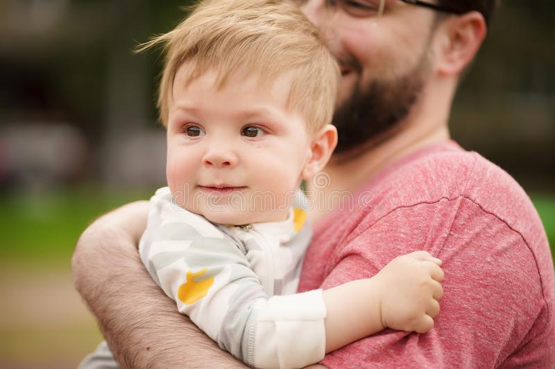 Close-up portrait of adorable baby smiling with his hipster father. Concept: family values. Close-up portrait of adorable innocent funny brown-eyed baby smiling stock images
