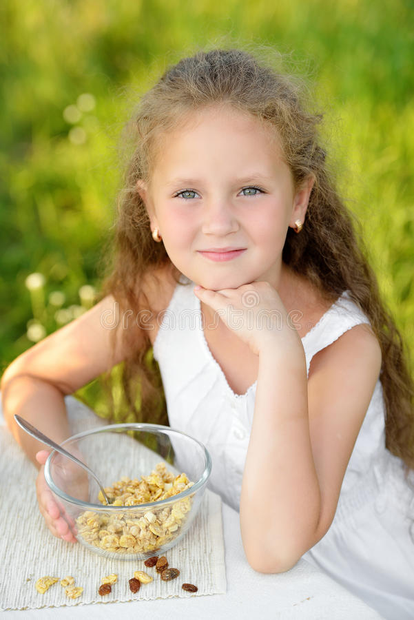 Close up portrait of adorable girl having breakfast and drinking milk outdoor. Cereal, healthy lifestyle stock images