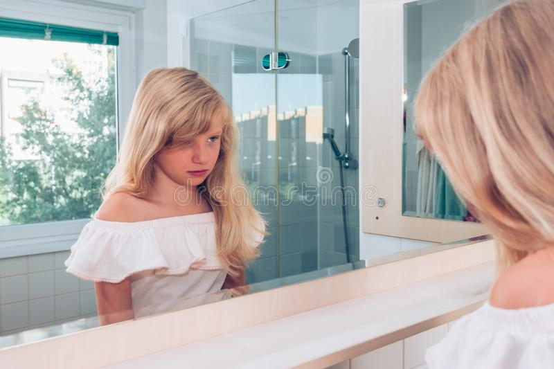 Sad blond girl alone in the bathroom looking into mirror stock images