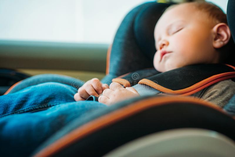 Close-up portrait of adorable little baby sleeping in child. Safety seat in car stock photo