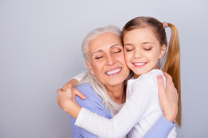 Close up portrait of adorable small lovely sweet charming beautiful girl hugging her careful attentive with white hair granny stock image