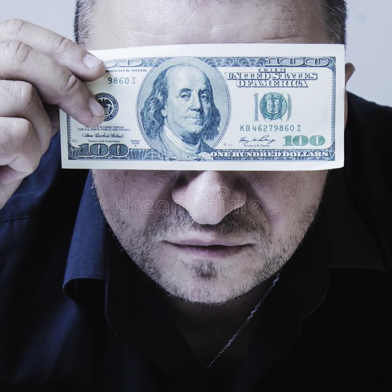 Close up portrait of adult brutal businessman holds US Dollar bills in front of eyes as if he wants to say: I see nothing but stock photos