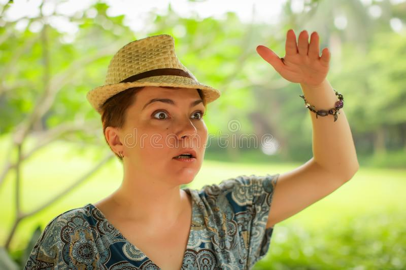 Close up portrait of adult caucasian woman in wicker hat posing with different emotions in green summer park stock image