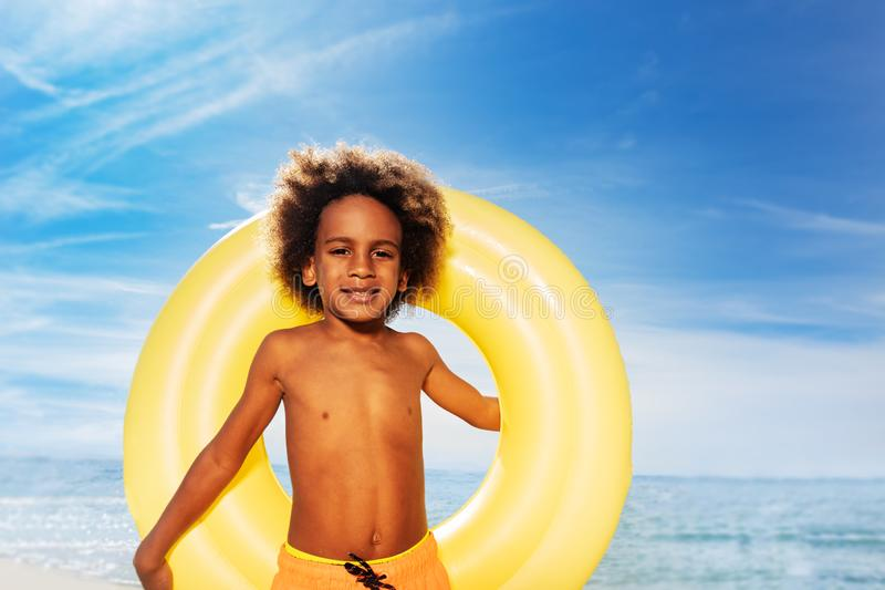 Cute African boy holding swim ring behind his back. Close-up portrait of African boy holding big swim ring behind his back, standing against exotic seascape and stock photo