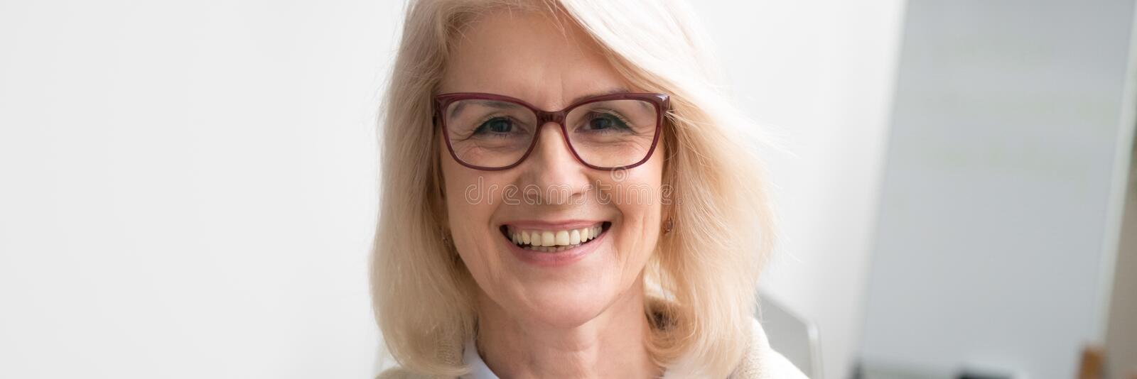 Horizontal image face of aged businesswoman smiling looking at camera stock photo