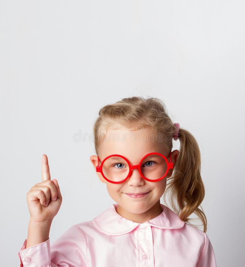 Close-up portrait of amazed pretty young girl schoolgirl in red glasses and a light blouse, pointing finger up, looking royalty free stock photography