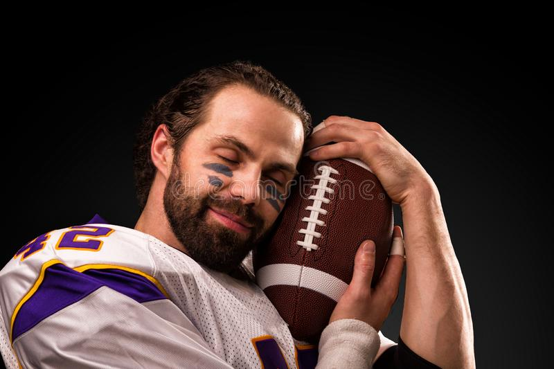 Close up portrait of American Football Player who gently holds the ball stock photography