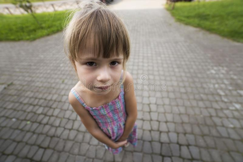 Close-up portrait, angled view from above of little blond pale unhappy moody friendless child girl stock image