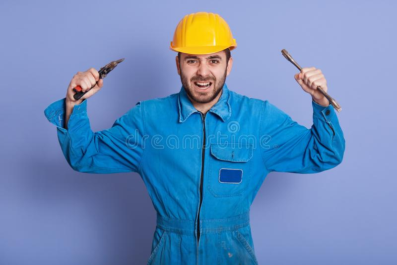 Close up portrait of angry construction worker engineer wearing yellow helmet and blue uniform, keeping hands up, shouting royalty free stock photography
