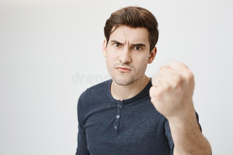Close-up portrait of angry handsome guy showing fist to camera, threatening someone while standing over gray background stock photography
